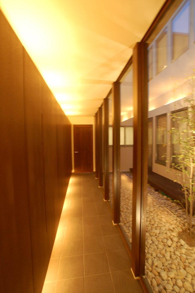 大江町の古い集落に建つ土壁の箱型フォルムとその奥に広がる中庭を囲む回廊の家