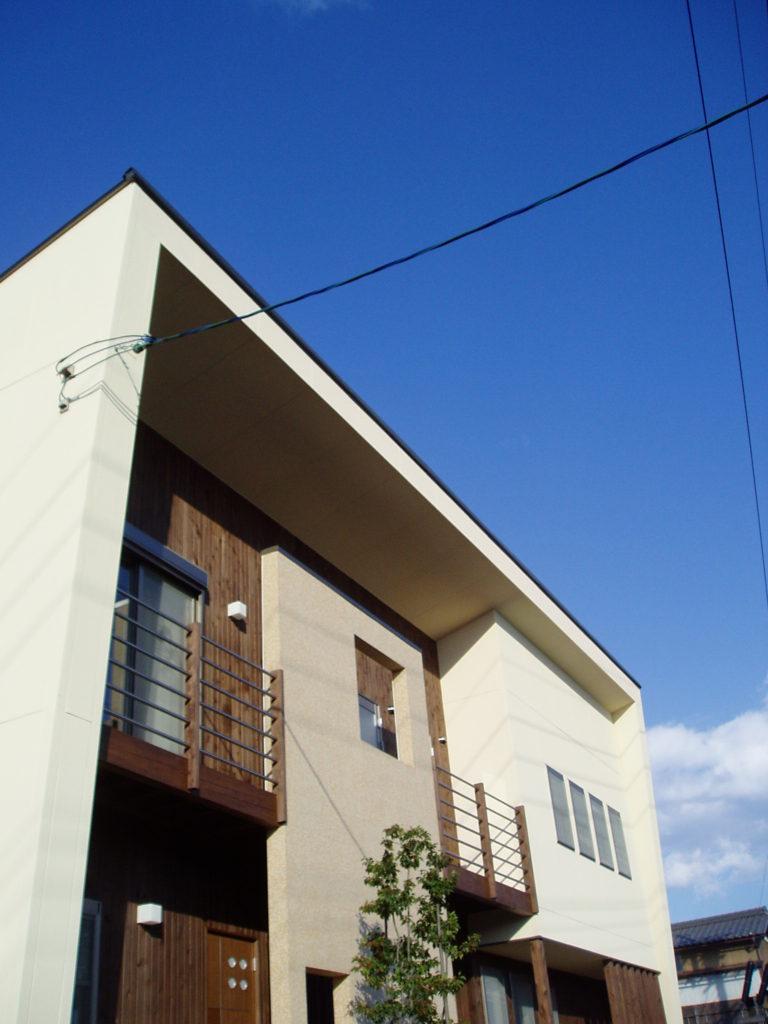 高台から遠くの景色を望む大きく突き出したオープンデッキを持つ家