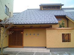 1階から2階まで伸びる大きな瓦屋根と土壁が特徴の邸宅